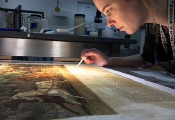 Third year student Allison Brewer works on pulp fills in the paper conservation lab.